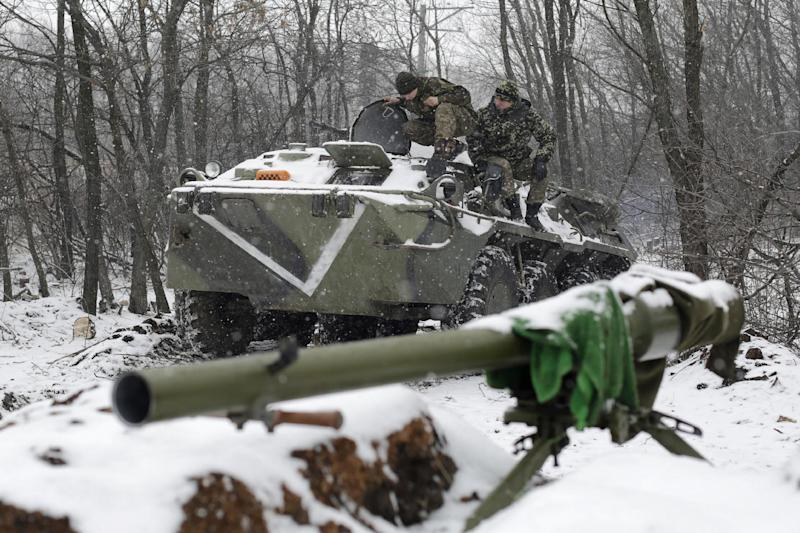 Ukrainian servicemen sit on a tank at a checkpoint near the town of Svitlodarsk, in the Donetsk region, on February 16, 2015