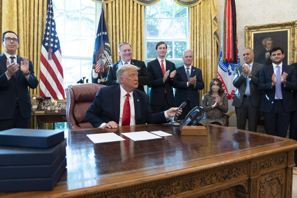 President Donald Trump hangs up a phone call with the leaders of Sudan and Israel, as Treasury Secretary Steven Mnuchin, left, Secretary of State Mike Pompeo, White House senior adviser Jared Kushner, National Security Adviser Robert O'Brien, and others applaud in the Oval Office of the White House, Friday, Oct. 23, 2020, in Washington. (AP Photo/Alex Brandon)