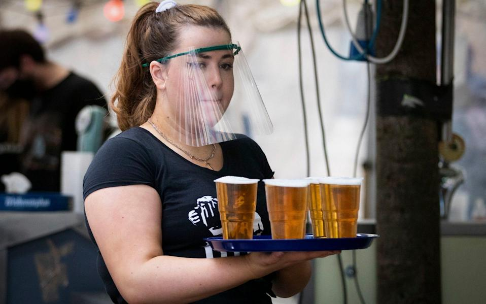 A member of staff serves drinks in the beer garden at the Bier Halle, Glasgow, when outdoor areas reopened last year - Jane Barlow/PA