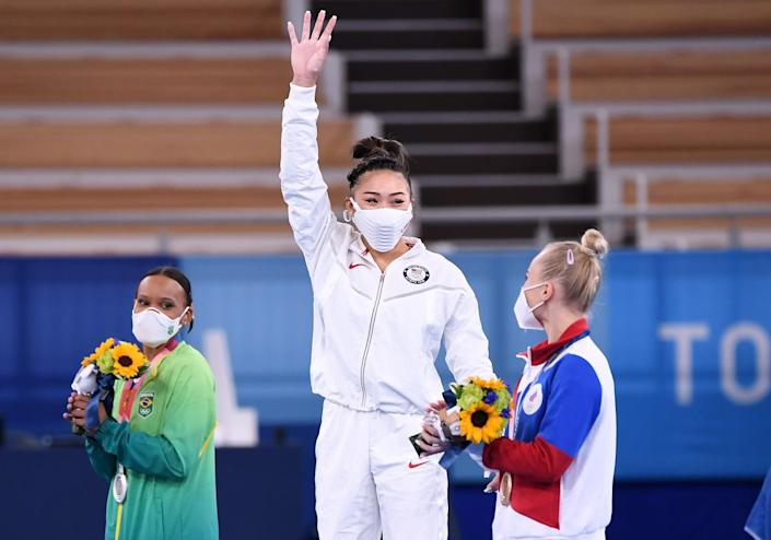 Suni Lee waves from the top of the medals podium.