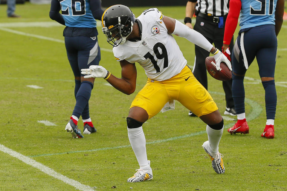 JuJu Smith-Schuster's socks come up to just under his knees with a portion of his leg exposed between pants and socks.