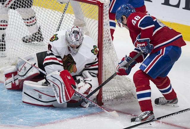 Chicago Blackhawks goalie Corey Crawford stops Montreal Canadiens' Daniel Briere during the second period of an NHL hockey game Saturday, Jan. 11, 2014, in Montreal. (AP Photo/The Canadian Press, Paul Chiasson)