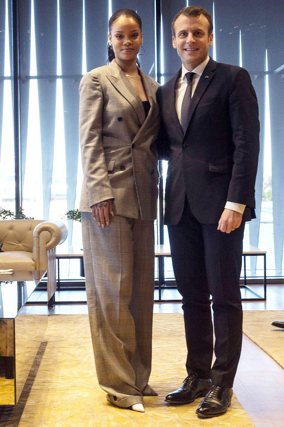 <p>Rihanna wears a gray plaid suit, white pumps, and thin gold necklaces while meeting Emmanuel Macron, the President of France, for a conference hosted by the Global Partnership for Education in Dakar, Senegal.</p>