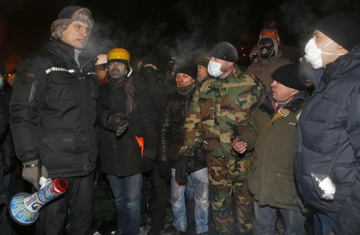 Opposition leader and former WBC heavyweight boxing champion Vitali Klitschko, left, addresses protesters near the barricades between police and protesters in central Kiev, Ukraine, early Friday Jan. 24, 2014. Emerging from hours-long talks with President Viktor Yanukovych, opposition leader Oleh Tyahnybok asked demonstrators in Kiev for several more days of a truce, saying the president has agreed to ensure the release of dozens of detained protesters and stop further detentions. (AP Photo/Sergei Grits)