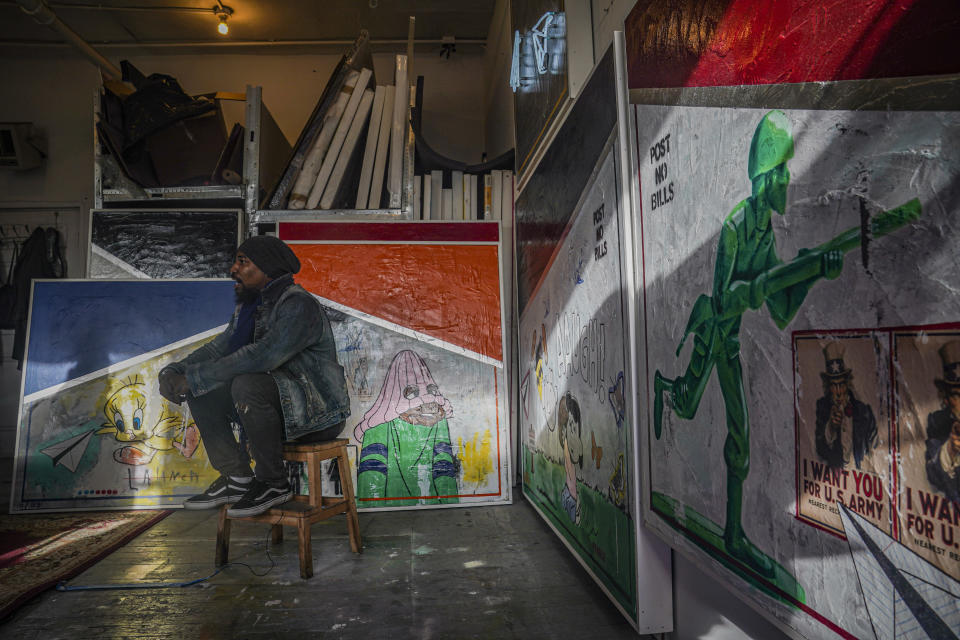 "Painter Guy Stanley Philoche, a 43-year-old Haitian immigrant and star in the New York art world, sit among some of his latest work during an interview at his East Harlem studio, Thursday Nov. 19, 2020, in New York. After a hugely successful gallery show, Philoche wanted to treat himself to a fancy $15,000 watch, instead he bought the works of fellow artists struggling in the pandemic. ""I'm not a rich man,"" he said, ""but I owe a big debt to the art world."" (AP Photo/Bebeto Matthews)"
