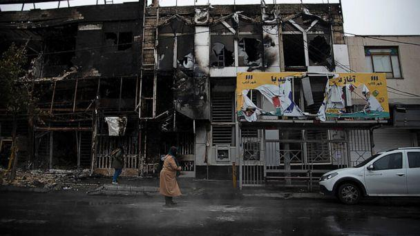 PHOTO: In this photo taken Nov. 18, 2019, and released by Iranian Students' News Agency, people walk past buildings which burned during protests that followed the authorities' decision to raise gasoline prices, in Karaj, west of the capital Tehran, Iran. (Masoume Aliakbar/ISNA via AP)