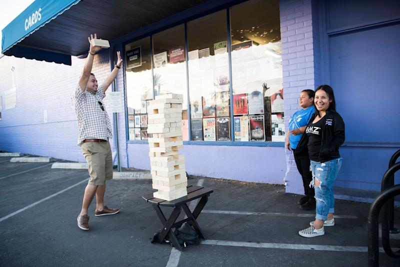 D.J. Munoz plays a game of jumbo Jenga with Ariel Munoz and Andrea Munoz.