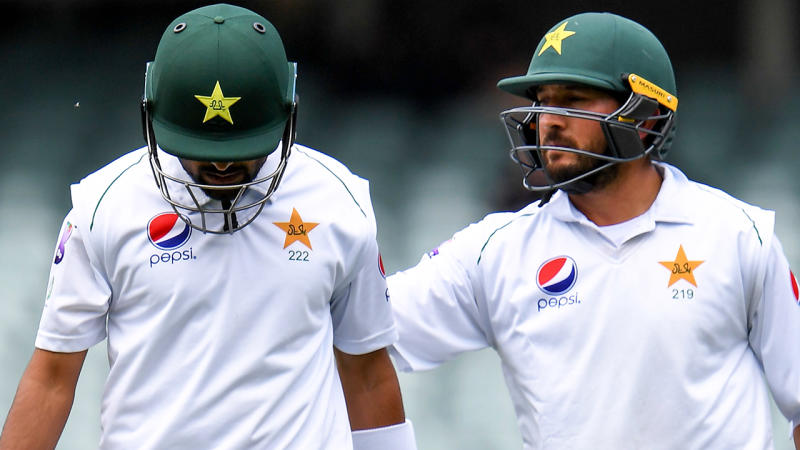 Pakistan batsman Babar Azam is consoled by teammate Yasir Shah after been dismissed by Australia for 97 runs on the third day of the second cricket Test match in Adelaide. (Photo by WILLIAM WEST/AFP via Getty Images)