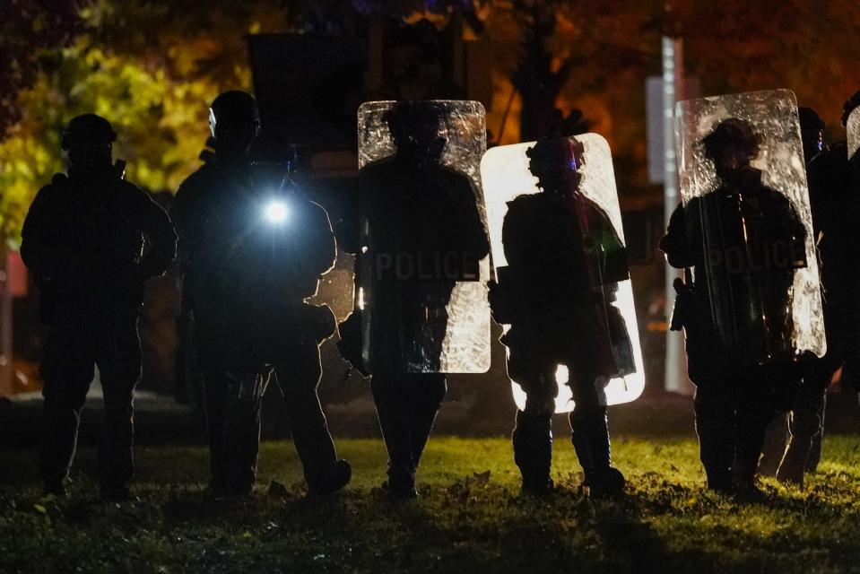Police in riot gear line up Friday, Oct. 9, 2020, during protests in Wauwatosa, Wis. On Wednesday, District Attorney John Chisholm declined to charge Wauwatosa police Officer Joseph Mensah in the February fatal shooting of 17-year-old Alvin Cole outside a mall. (AP Photo/Morry Gash)