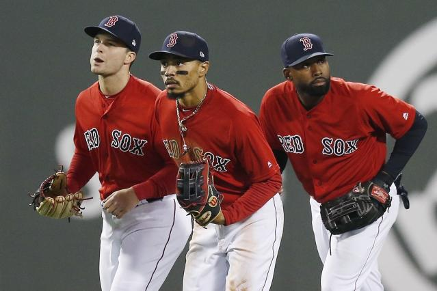 "FILE - In this Friday, April, 12, 2019 file photo, Boston Red Sox's Andrew Benintendi, left, Mookie Betts, center, and Jackie Bradley Jr. run in after defeating the Baltimore Orioles during a baseball game in Boston. When the Boston Red Sox traded Mookie Betts to the Los Angeles Dodgers on the eve of spring training, they broke up the ""Killer B's who patrolled the Fenway outfield and led the team to a World Series championship in 2018. Together, Betts, Jackie Bradley Jr. and Andrew Benintendi formed one of the best outfields in baseball. (AP Photo/Michael Dwyer, File)"