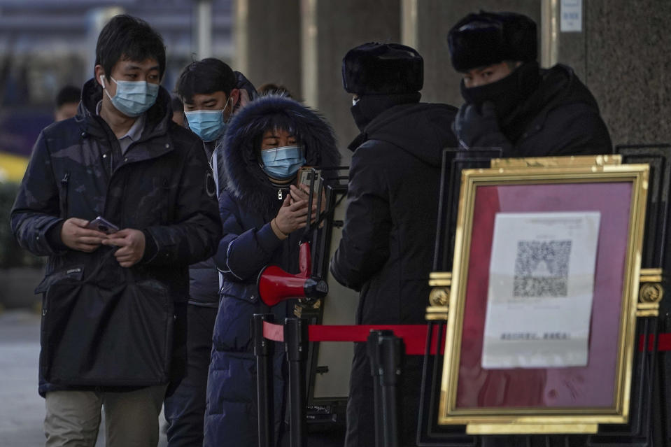 People wearing face masks to help curb the spread of the coronavirus use smartphones to scan their health code before entering an office building in Beijing, Tuesday, Jan. 12, 2021. Lockdowns have been expanded and a major political conference postponed in a province next to Beijing that is the scene of China's most serious recent COVID-19 outbreak. (AP Photo/Andy Wong)