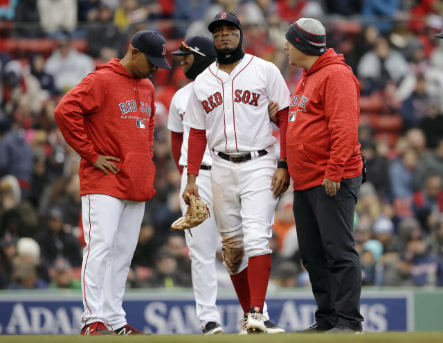 Xander Bogaerts, center, is assisted as he leaves the field as manager Alex Cora, left, looks on in the seventh inning of a baseball game against the Tampa Bay Rays on Sunday. (AP)