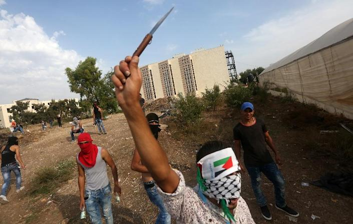 A Palestinian youth raises a knife during clashes with Israeli security forces (unseen) in the West Bank city of Tulkarem on October 18, 2015 (AFP Photo/Jaafar Ashtiyeh)
