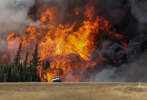 Smoke and flames from wildfires erupt behind a car on the highway near Fort McMurray, Alta., on May 7, 2016. (Mark Blinch/Reuters - image credit)