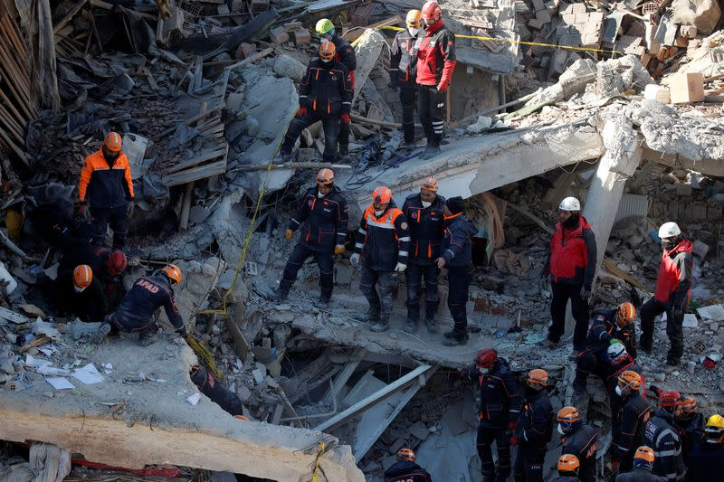 Rescue workers search the site of a collapsed building, after an earthquake in Elazig