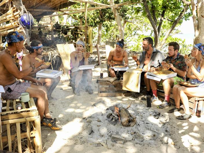 Survivor players sitting at camp and eating pizza out of boxes, with the forest in the background