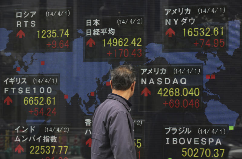 A man looks at an electronic stock board of a securities firm in Tokyo Wednesday, April 2, 2014. Asian stock markets pushed higher Wednesday on signs of a pickup in the U.S. economy and expectations of further stimulus in Japan. Tokyo's Nikkei 225 closed at 14,946.32, after gaining 154.33 points, or 1.04 percent. (AP Photo/Eugene Hoshiko)