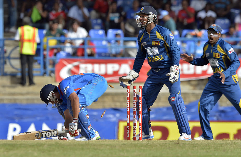 Indian batsman Rohit Sharma (R) is clean bowled off Sri Lankan bowler Rangana Herath during the final match of the Tri-Nation series between India and Sri Lanka at the Queen's Park Oval stadium in Port of Spain on July 11, 2013. Sri Lanka have scored 201/10. AFP PHOTO/Jewel Samad