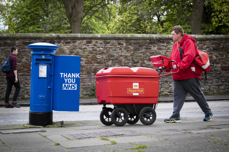 Postman Graeme Byers passes by one of the specially decorated postboxes in Edinburgh painted blue in support of NHS workers and carers fighting the coronavirus pandemic. (Photo by Jane Barlow/PA Images via Getty Images)