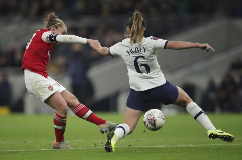 Arsenal's Kim Little, left, scores her sides first goal of the match against Tottenham Hotspur, during their Women's Super League soccer match at the Tottenham Hotspur Stadium in London, Sunday Nov. 17, 2019.  The match drew a record crowd of 38,262 for the competition on Sunday when Arsenal claimed a 2-0 victory at Tottenham. (Zac Goodwin/PA via AP)