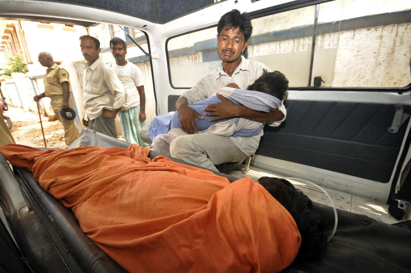 An Indian man mourns as he holds his dead daughter inside an ambulance, outside a hospital in Patna, in the eastern Indian state of Bihar, Wednesday, July 17, 2013. Officials on Wednesday blamed the presence of insecticide in a free midday meal after at least 20 children died and many more were sick after eating lunch at a primary school in the eastern Indian state of Bihar. The children are age 8 to 11. (AP Photo/Aftab Alam Siddiqui)
