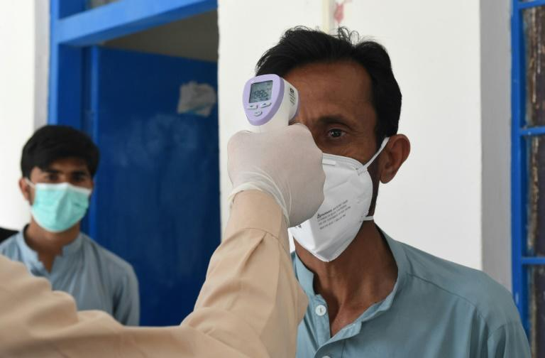 A doctor checks the temperature of a man on February 25 as he returns from Iran to Pakistan, where two cases of novel coronavirus have been confirmed