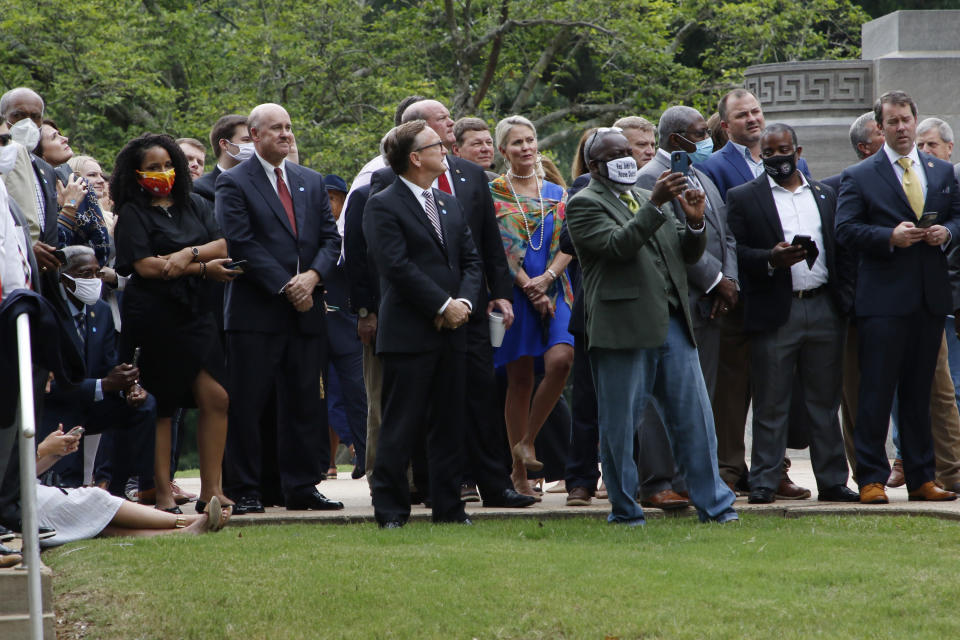 Lawmakers, Capitol employees, spectators and media watch as the retired Mississippi state flag is raised over the Capitol grounds one final time in Jackson, Miss., Wednesday, July 1, 2020. The banner was the last state flag with the Confederate battle emblem on it. (AP Photo/Rogelio V. Solis)