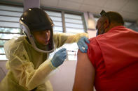 FILE - In this March 10, 2021 file photo, a healthcare worker injects a man with a dose of the Moderna COVID-19 vaccine during a mass vaccination campaign, at the Maria Simmons elementary school in Vieques, Puerto Rico. A spike in cases and hospitalizations has put medical experts at odds with the government, which is struggling to protect people's health while also trying to prevent an economic implosion on an island battered by hurricanes, earthquakes and a prolonged financial crisis. (AP Photo/Carlos Giusti, File)