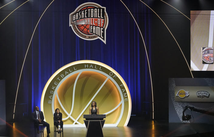 Tamika Catchings speaks while being inducted with 2020 Basketball Hall of Fame class, Saturday, May 15, 2021, in Uncasville, Conn. Catchings' presenters, Alonzo Mourning, left, and Dawn Staley, second from left, listen. (AP Photo/Kathy Willens)