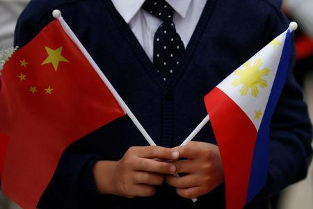 A child holds national flags of China and the Philippines in Beijing