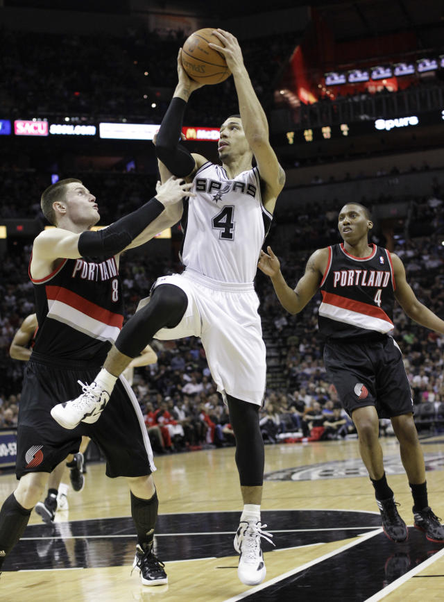 San Antonio Spurs' Danny Green (4) goes up between Portland Trail Blazers' Luke Babbitt (8) and Nolan Smith (4) during the first quarter of an NBA basketball game, Monday, April 23, 2012, in San Antonio. San Antonio won 124-89. (AP Photo/Eric Gay)