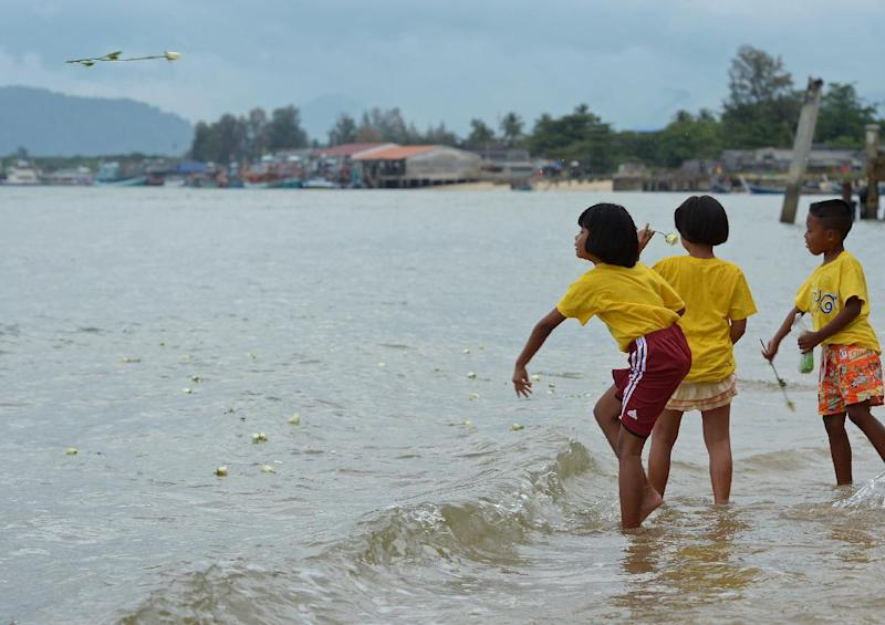 Children throw roses into the sea near the Ban Nam Khem tsunami memorial park as the 10th anniversary of the 2004 tsunami is remembered in Phang-nga province in Thailand, on December 26, 2014 (AFP Photo/Pornchai Kittiwongsakul)