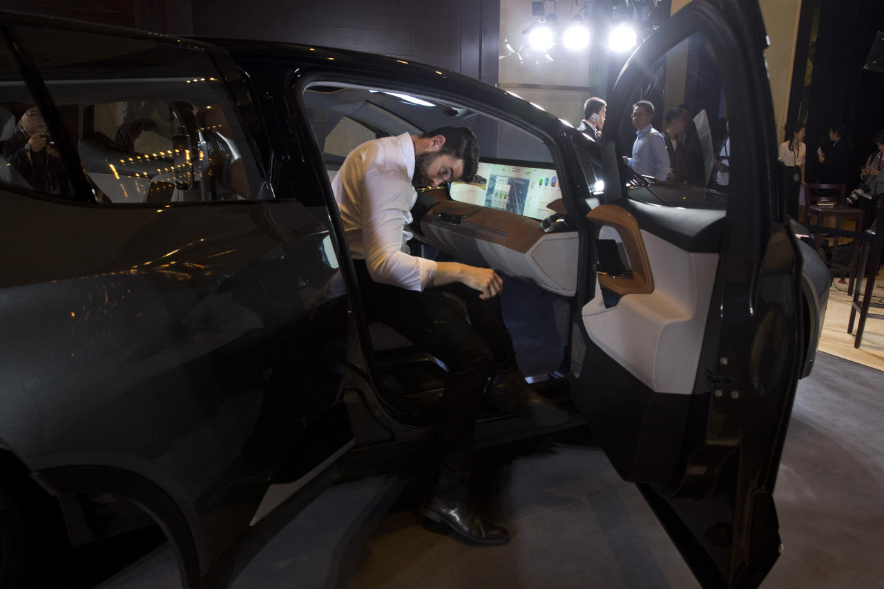 In this April 20, 2018, photo, a worker examines the interior of the BYTON electric concept car during a press event held ahead of the Auto China 2018 in Beijing, China. Auto China 2018, the biggest global auto show of the year, showcases China's ambitions to become a leader in electric cars and the industry's multibillion-dollar scramble to roll out models that appeal to price-conscious but demanding Chinese drivers. (AP Photo/Ng Han Guan)