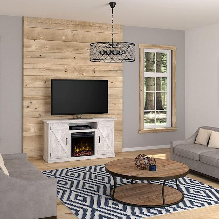 """<p><strong>Twin Star Home</strong></p><p>amazon.com</p><p><strong>$329.99</strong></p><p><a href=""""https://www.amazon.com/Comfort-Smart-Killian-Electric-Fireplace/dp/B07BDRN9HP/?tag=syn-yahoo-20&ascsubtag=%5Bartid%7C10060.g.37621995%5Bsrc%7Cyahoo-us"""" rel=""""nofollow noopener"""" target=""""_blank"""" data-ylk=""""slk:Shop Now"""" class=""""link rapid-noclick-resp"""">Shop Now</a></p><p><strong>Key Specs</strong></p><ul><li><strong>Dimensions</strong>: 47.5 x 15.5 x 27 inches</li><li><strong>Main material</strong>: Manufactured wood</li><li><strong>Weight capacity</strong>: 40 pounds</li><li><strong>Max TV screen size: </strong>55 inches</li><li><strong>Adjustable shelves</strong>: Yes</li></ul><p>For a truly rustic fireplace TV stand, this option—which is available in a handful of light and dark neutral hues—will add cozy vibes to a contemporary family room. It supports TVs up to 55 inches and features two barn-door-inspired cabinets with traditional pewter hardware, which pair well with the stand's creamy distressed finish. The cabinets offer ample storage space, and each have a single adjustable shelf. </p><p>There's only one setting for the 18-inch-wide electric fireplace set in the center, though several customers note that it puts out a good amount of heat. The only downside—though likely not a dealbreaker—is that it doesn't come with a remote control. </p>"""