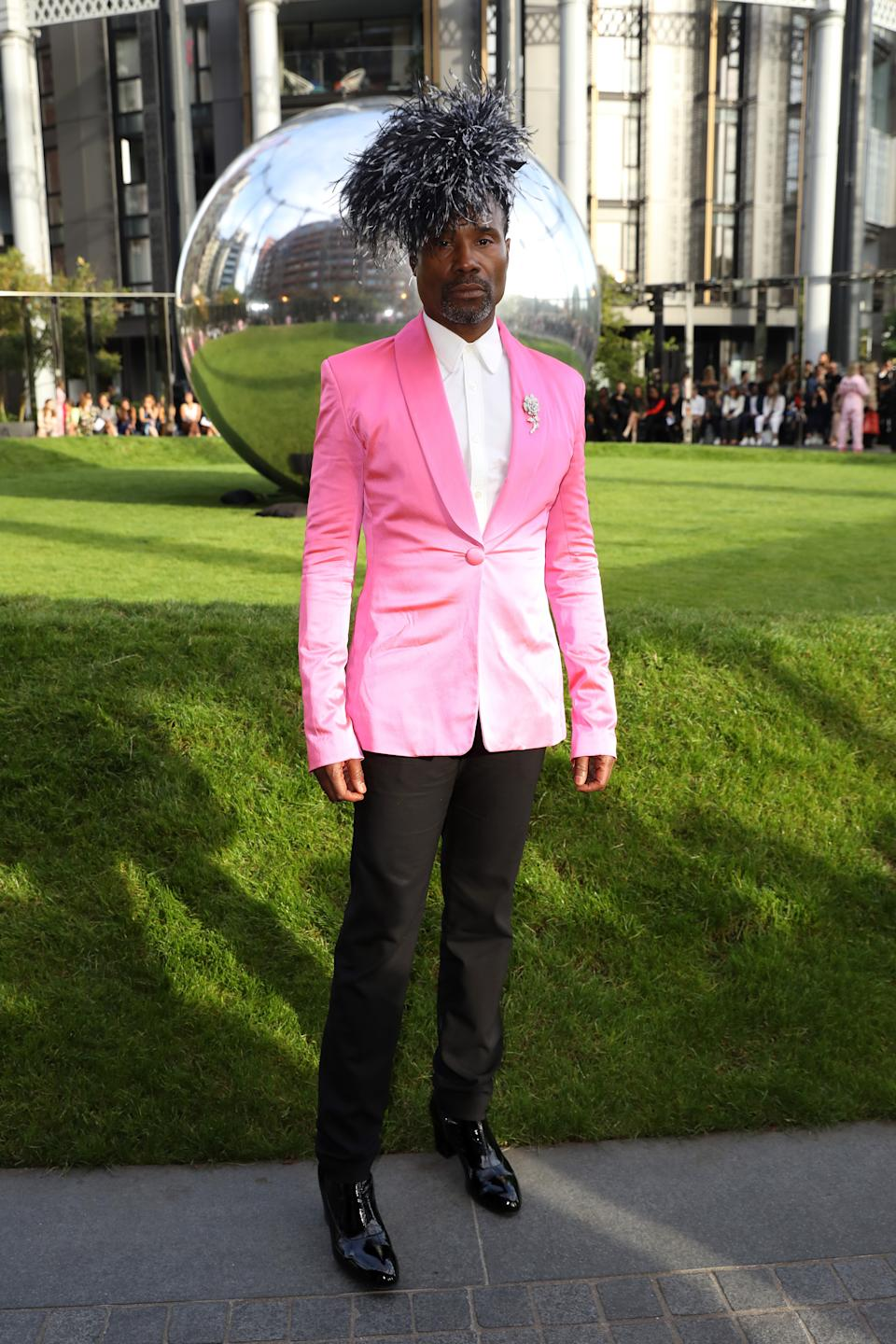Billy Porter attends the House of Holland wearing a pink tuxedo jacket, black trousers and a monochrome fascinator [Photo: Getty Images]