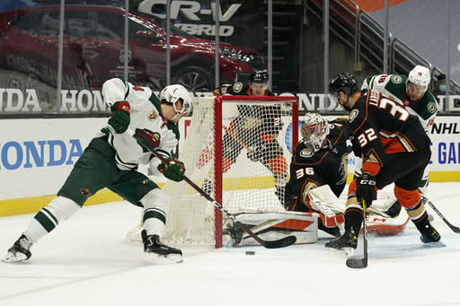 Anaheim Ducks goaltender John Gibson, center, stops a shot from Minnesota Wild center Joel Eriksson Ek during the first period of an NHL hockey game Monday, Jan. 18, 2021, in Anaheim, Calif. (AP Photo/Marcio Jose Sanchez)