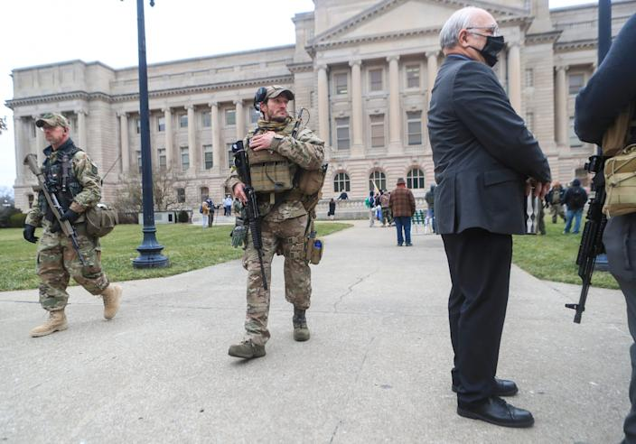 """As armed members of the Three Percenters patrol the grounds, Kentucky state Sen. Michael Nemes talks to other protesters on Saturday at a """"patriot rally"""" outside the state Capitol in Frankfort."""