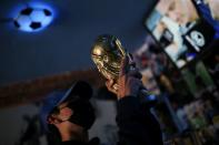 A fan holds up a replica of the World Cup trophy at the first Mexico's church in memory of soccer legend Diego Armando Maradona in San Andres Cholula