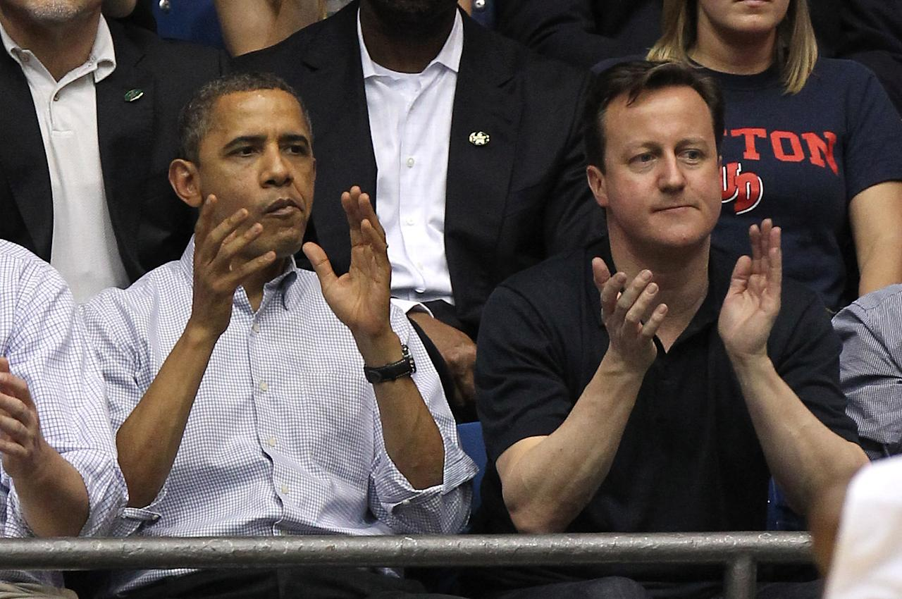 DAYTON, OH - MARCH 13:  U.S. President Barack Obama (L) and British Prime Minister David Cameron (R) clap at UD Arena in the first half as the Western Kentucky Hilltoppers take on the Mississippi Valley State Delta Devils in the first round of the 2011 NCAA men's basketball tournament on March 13, 2012 in Dayton, Ohio.  (Photo by Gregory Shamus/Getty Images)