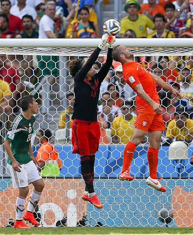 Mexico's goalkeeper Guillermo Ochoa goes up to clear the ball away from Netherlands' Ron Vlaar during the World Cup round of 16 soccer match between the Netherlands and Mexico at the Arena Castelao in Fortaleza, Brazil, Sunday, June 29, 2014. (AP Photo/Eduardo Verdugo)