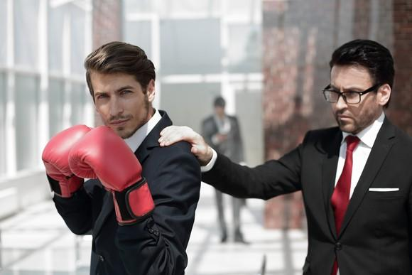 One businessman wearing boxing gloves while another puts a calming hand on the boxer's shoulder.