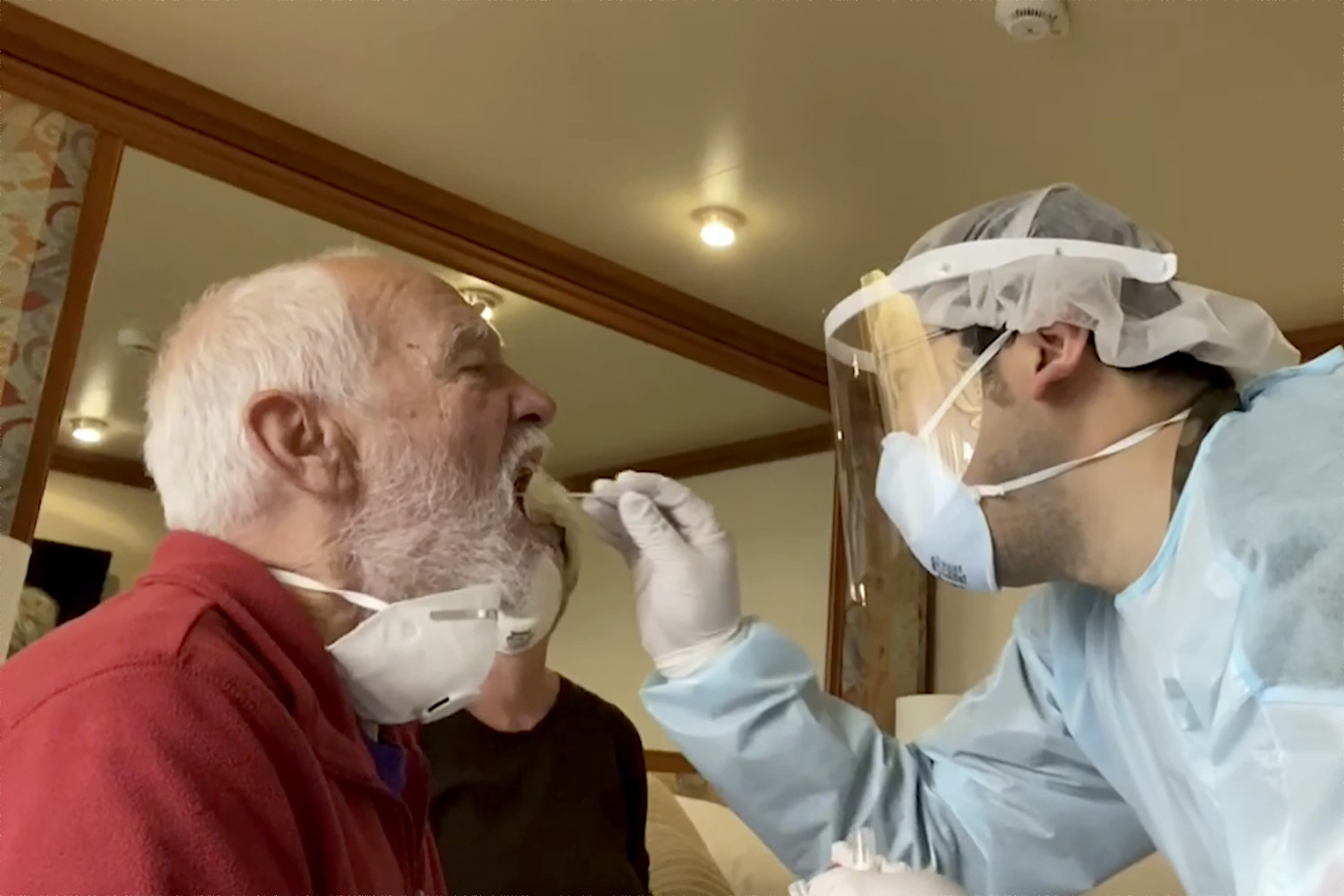 In this image from a video, Paul Molesky, left, gets a DNA swab test in his cabin room on the Diamond Princess, anchored at a port in Yokohama, near Tokyo Thursday, Feb. 13, 2020. Even during the quarantine, it can seem like Cheryl and Paul Molesky are still on vacation.(Cheryl and Paul Molesky via AP)
