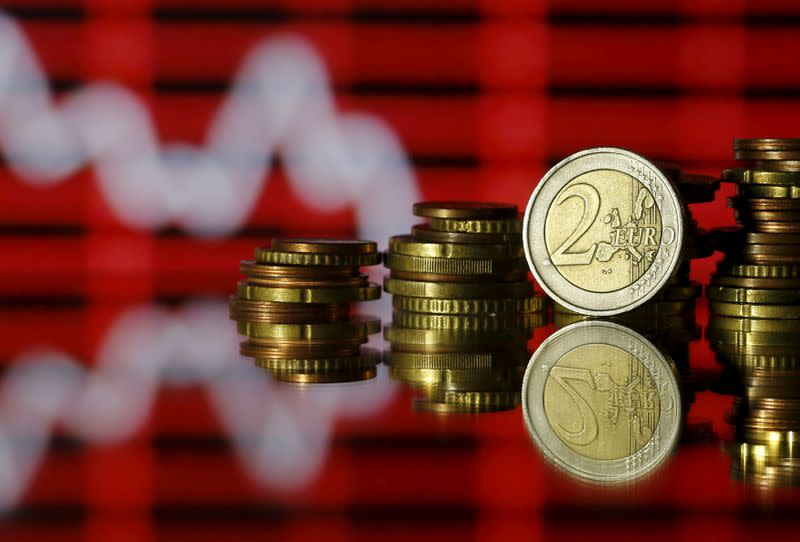Euro coins are seen in front of a displayed stock graph in this photo illustration