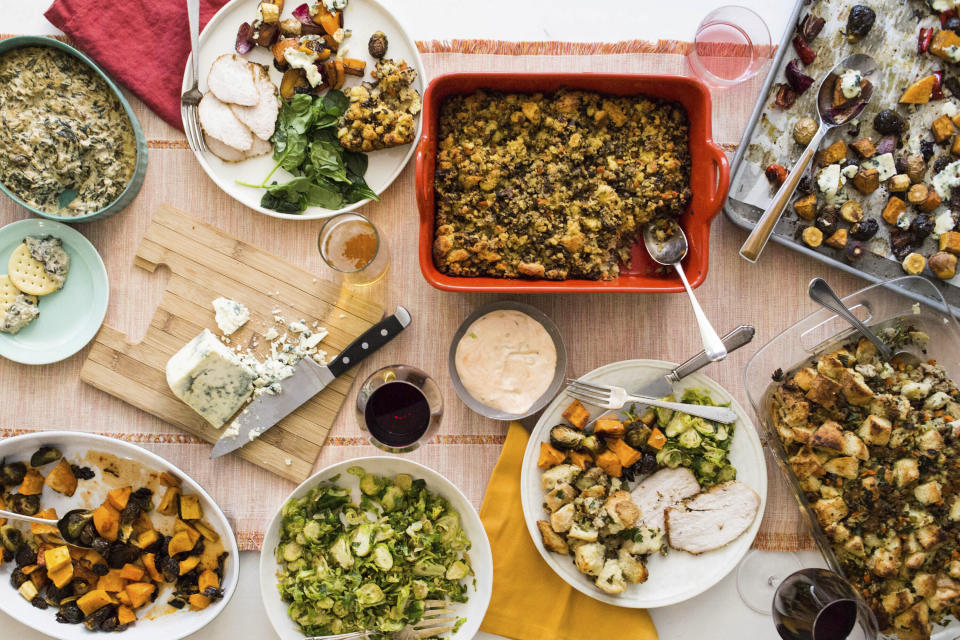 This October 2017 photo taken in New York, shows a Thanksgiving spread with hot spinach and mushroom dip, turkey, cornbread stuffing and sauteed brussel sprouts. A meal like this can be cooked and readied to be enjoyed in multiple homes and connected via Zoom, or virtually, during this year's Thanksgiving holiday. (Sarah Crowder/Katie Workman via AP)