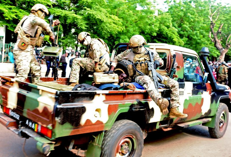 An assailant who attempted to stab Mali's interim president Colonel Assimi Goita, is seen lying in an army vehicle after he was arrested in Bamako