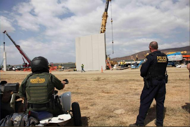 <p>A handout photo made available by U.S. Customs and Border Protection shows border patrol agents watching the construction of prototypes of the proposed border wall between the U.S. and Mexico near Otay Mesa, Calif., Oct. 3, 2017. (Photo: U.S. Customs and Border Protection/EPA-EFE/REX/Shutterstock) </p>