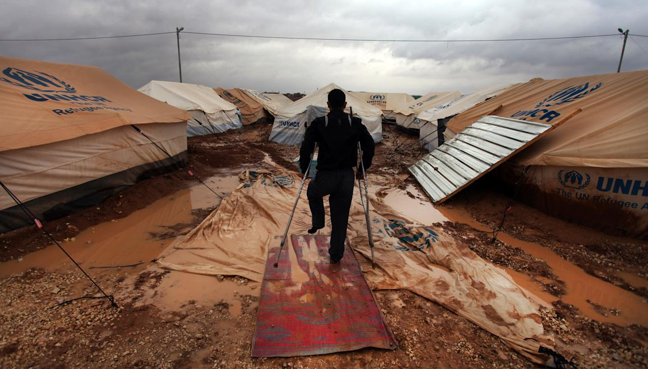 A Wounded Syrian refugee man makes his way on water and mud, at Zaatari Syrian refugee camp, near the Syrian border in Mafraq, Jordan, Tuesday, Jan. 8, 2013. Syrian refugees in a Jordanian camp attacked aid workers with sticks and stones on Tuesday, frustrated after cold, howling winds swept away their tents and torrential rains flooded muddy streets overnight. Police said seven aid workers were injured. (AP Photo/Mohammad Hannon)
