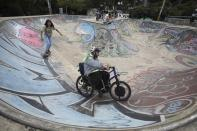 Martin Londoño, right, owner of MATT, an electric wheelchair tour company, rides his wheelchair at a skate park in Medellin, Colombia, Wednesday, Nov. 18, 2020. Londoño says he is trying to promote his tour on social media while building partnerships with local travel companies. He dreams of taking the wheelchair tours to other cities in Colombia, Latin America and the United States. (AP Photo/Fernando Vergara)