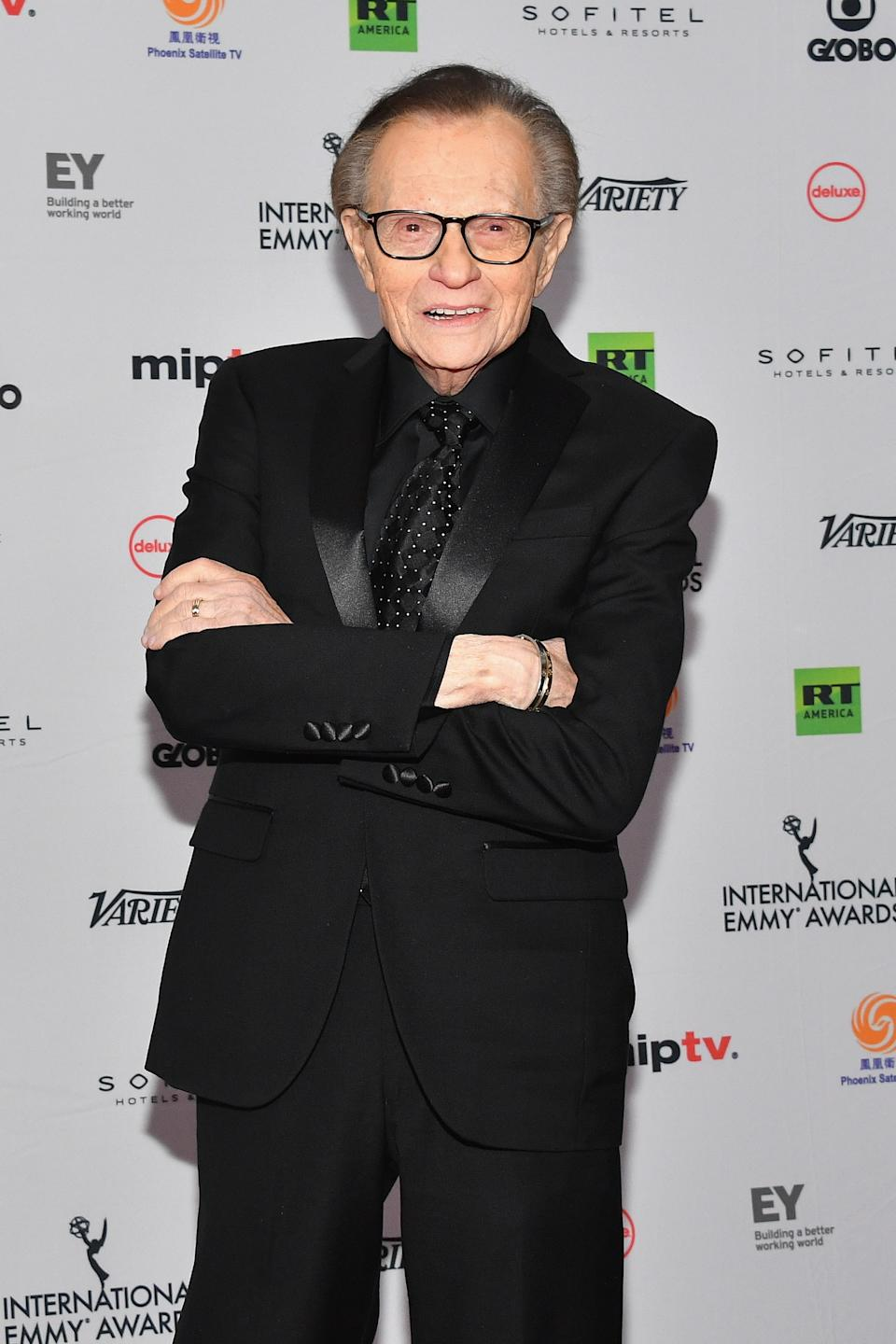 Larry King poses in black suit on red carpet