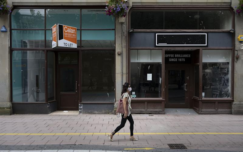 A woman wearing a surgical face mask walks passed closed shops on Queen Street on August 4, 2020 in Cardiff, United Kingdom - Matthew Horwood/Getty Images